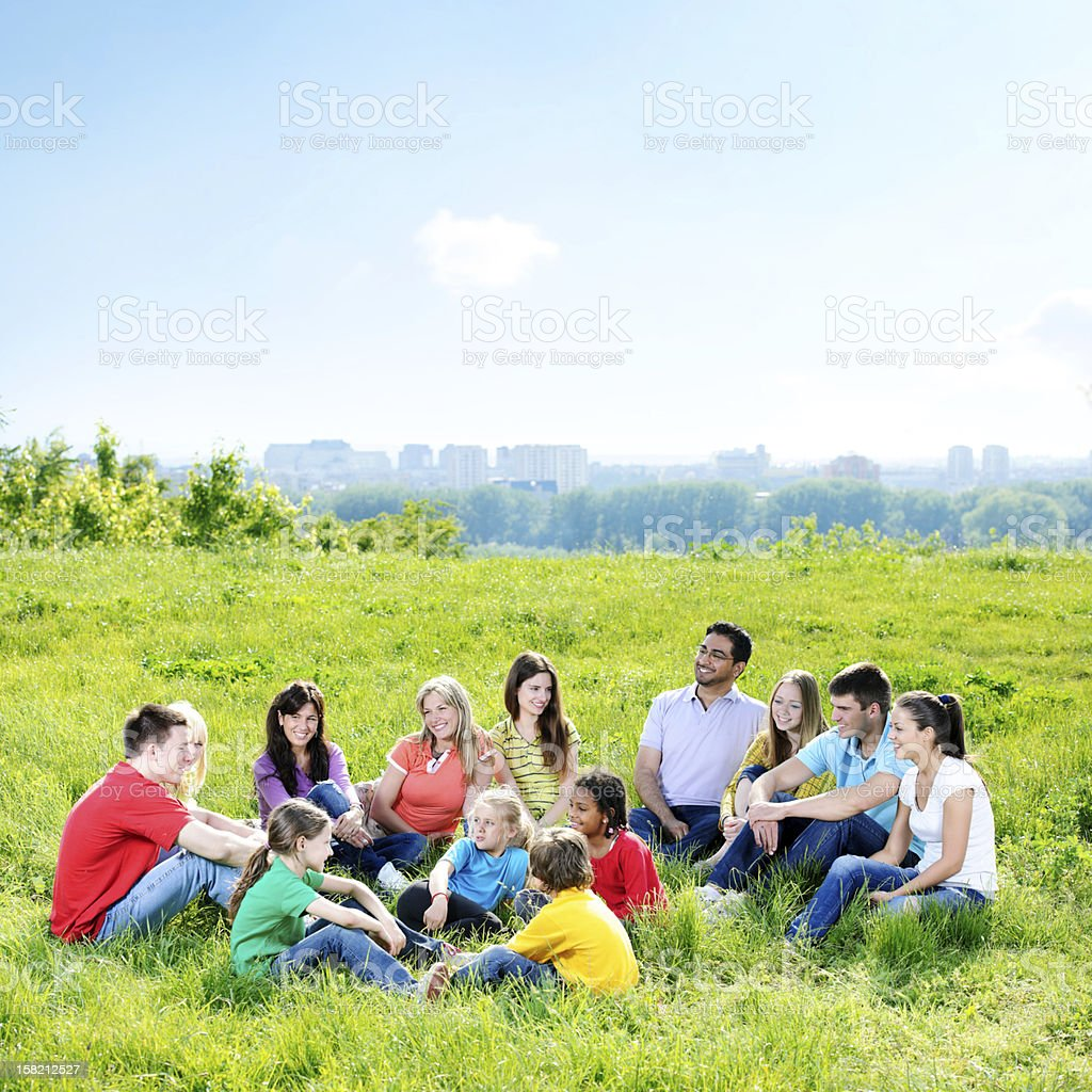 Large group of cheerful people sitting in the nature. royalty-free stock photo