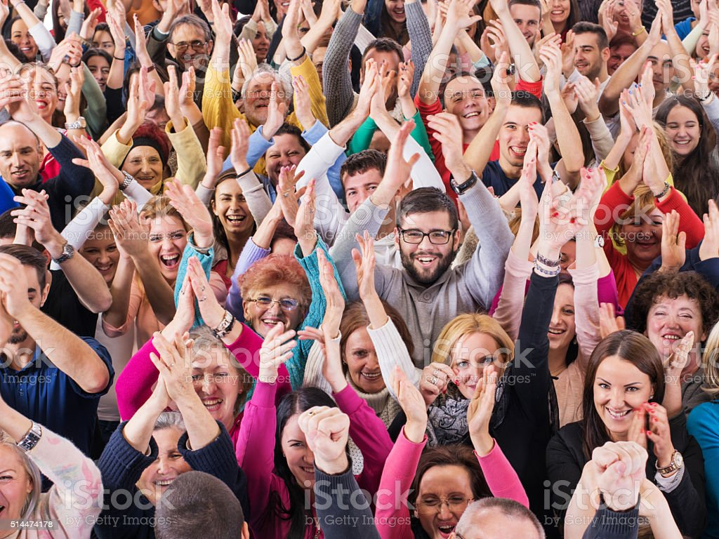 Large group of cheerful people with their arms outstretched. stock photo