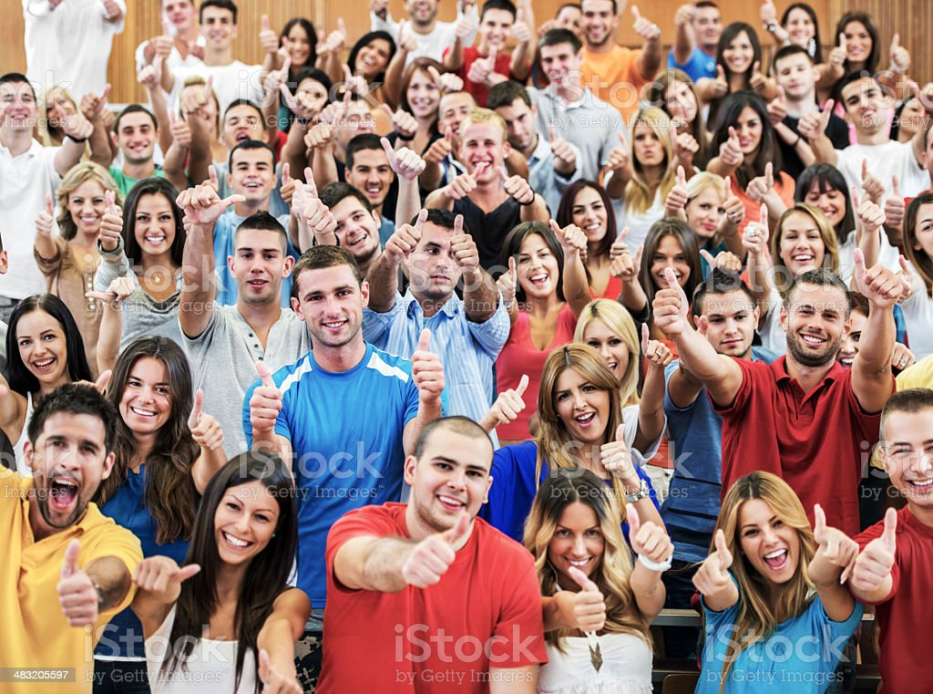 Large group of cheerful students showing thumbs up. stock photo