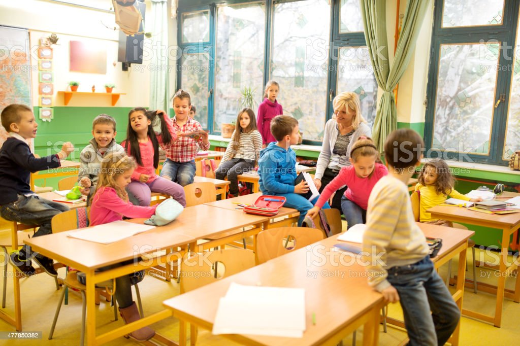 Large group of elementary students having a break at classroom. stock photo