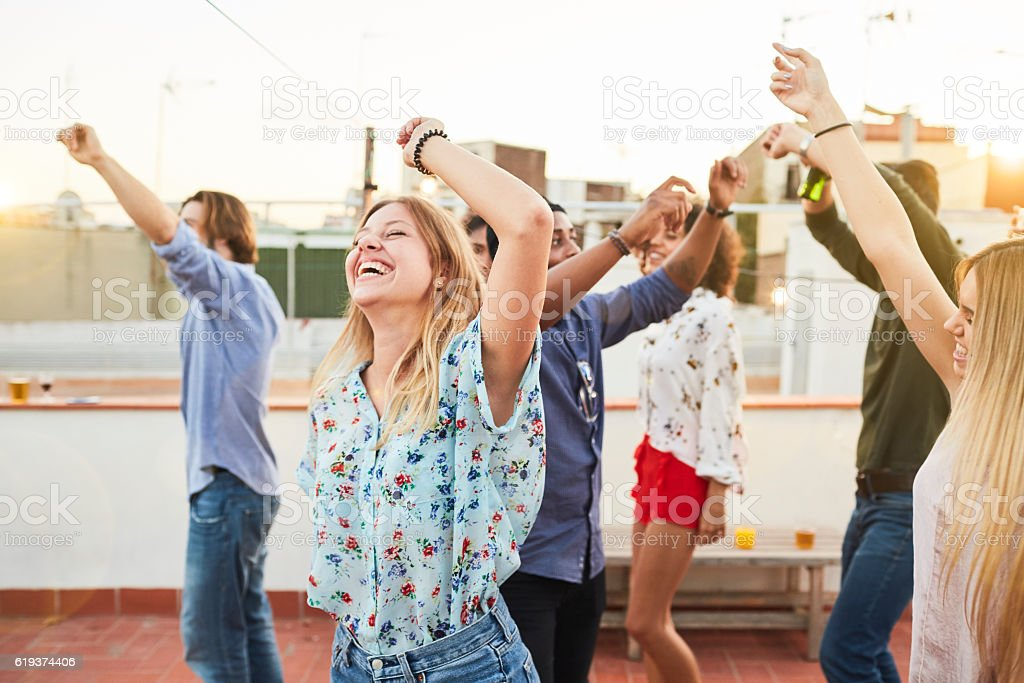 Large group of friends dancing and celebrating a rooftop party. stock photo