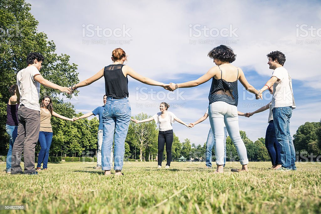 Large group of friends holding hands each other in circle stock photo