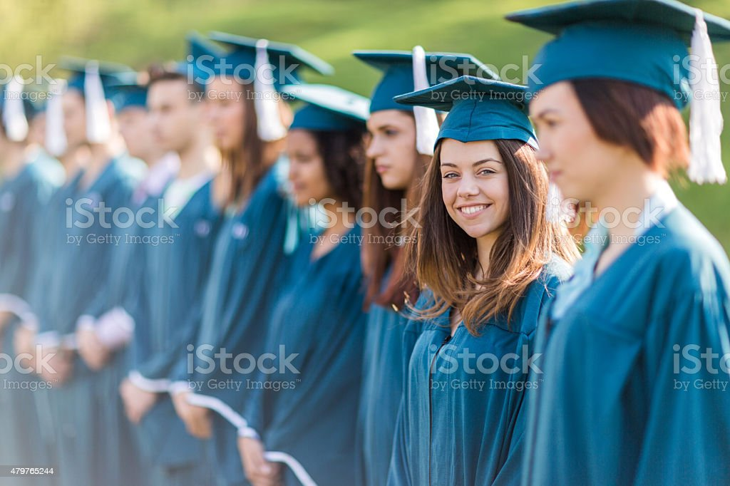 Large group of graduation students standing in a row outdoors. stock photo