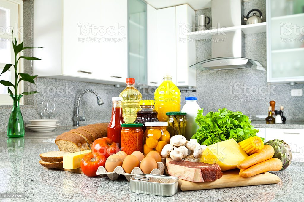 Large group of groceries on kitchen countertop stock photo