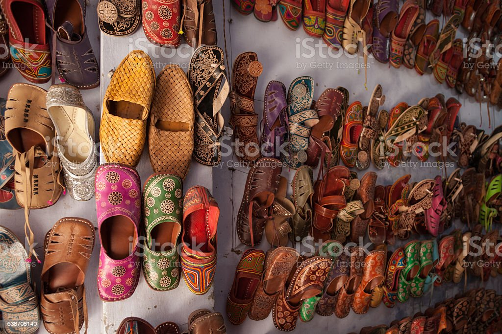 Large Group Of Handmade Indian Shoes On Wall stock photo