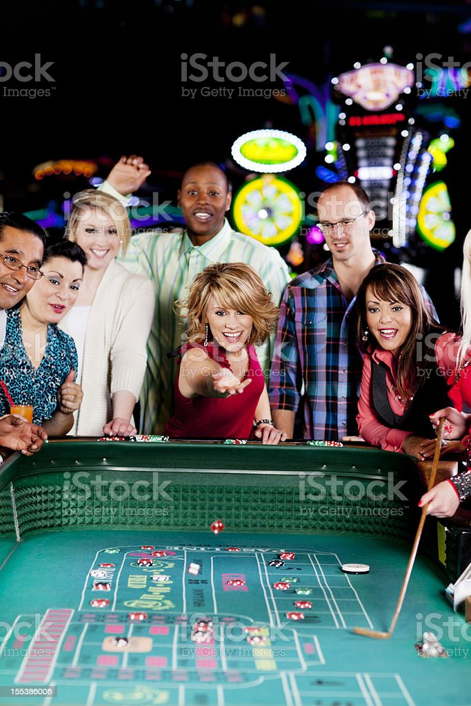 Large group of happy diverse people at the craps table stock photo