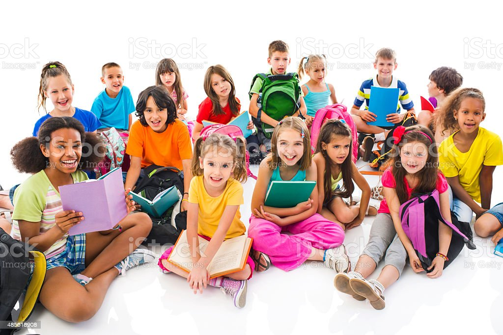 Large group of happy elementary students looking at camera. stock photo