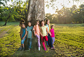 Large group of happy kids standing around the tree.