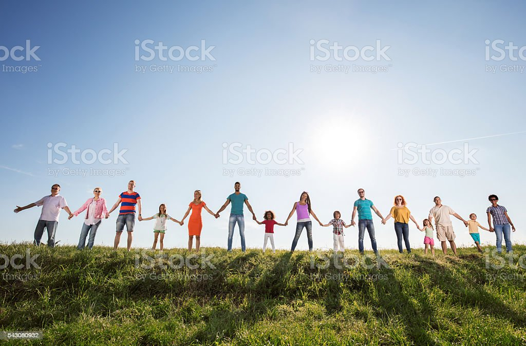 Large group of happy people holding hands against the sky. stock photo