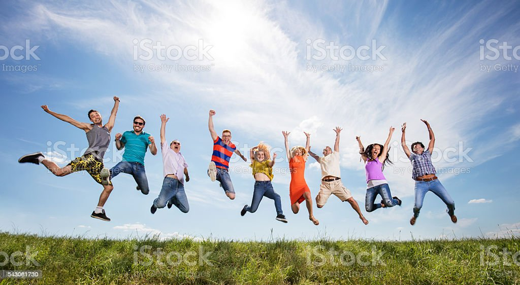 Large group of cheerful people with arms raised jumping high up...