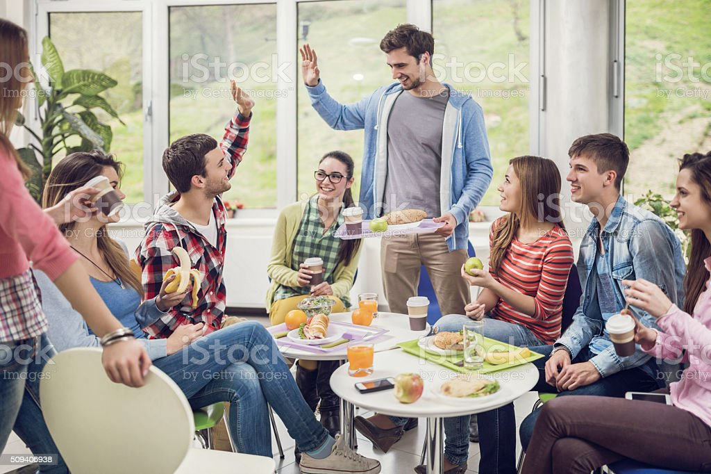 Large group of happy students in cafeteria during lunch break. stock photo