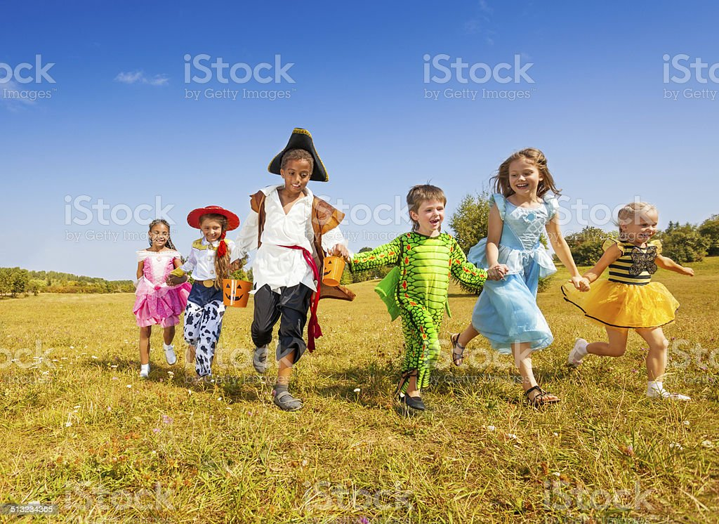 Large group of kids in Halloween costumes run stock photo