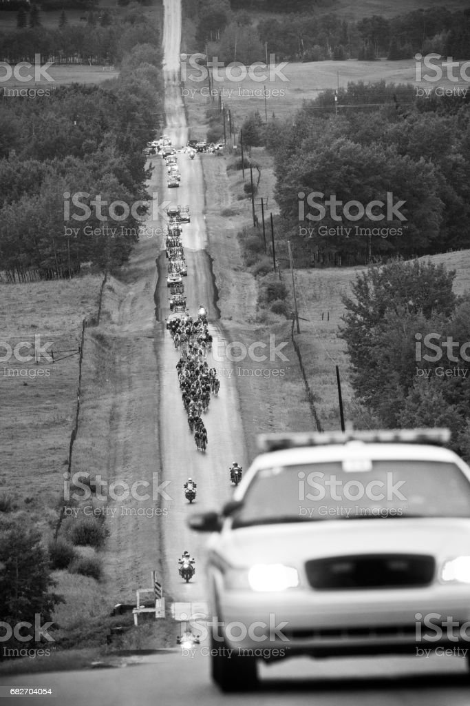 A large group of male bicycle racers ride together in a peloton during a professional road bike race. stock photo