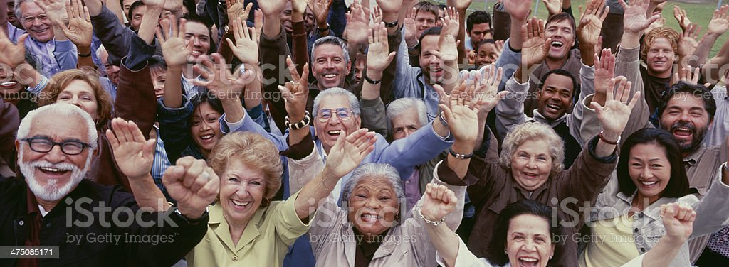 Large group of multi-ethnic people cheering with arms raised stock photo