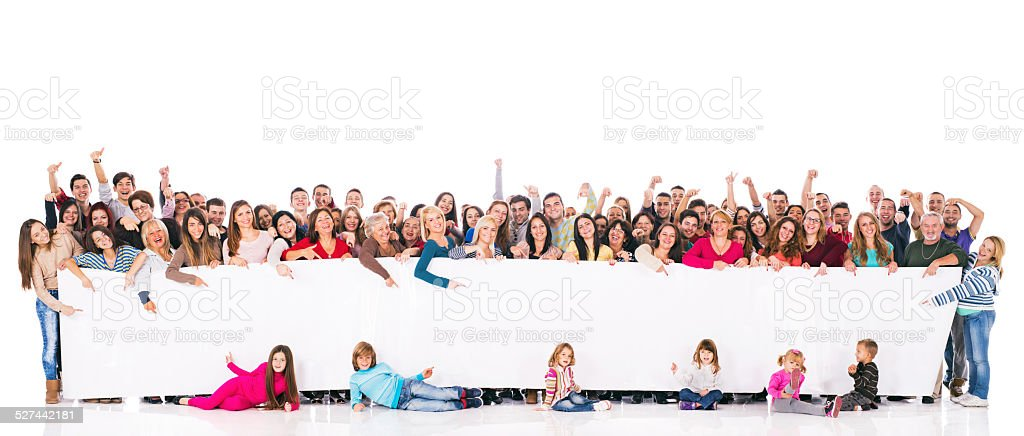 Large group of mixed-age people holding big white banner and pointing...