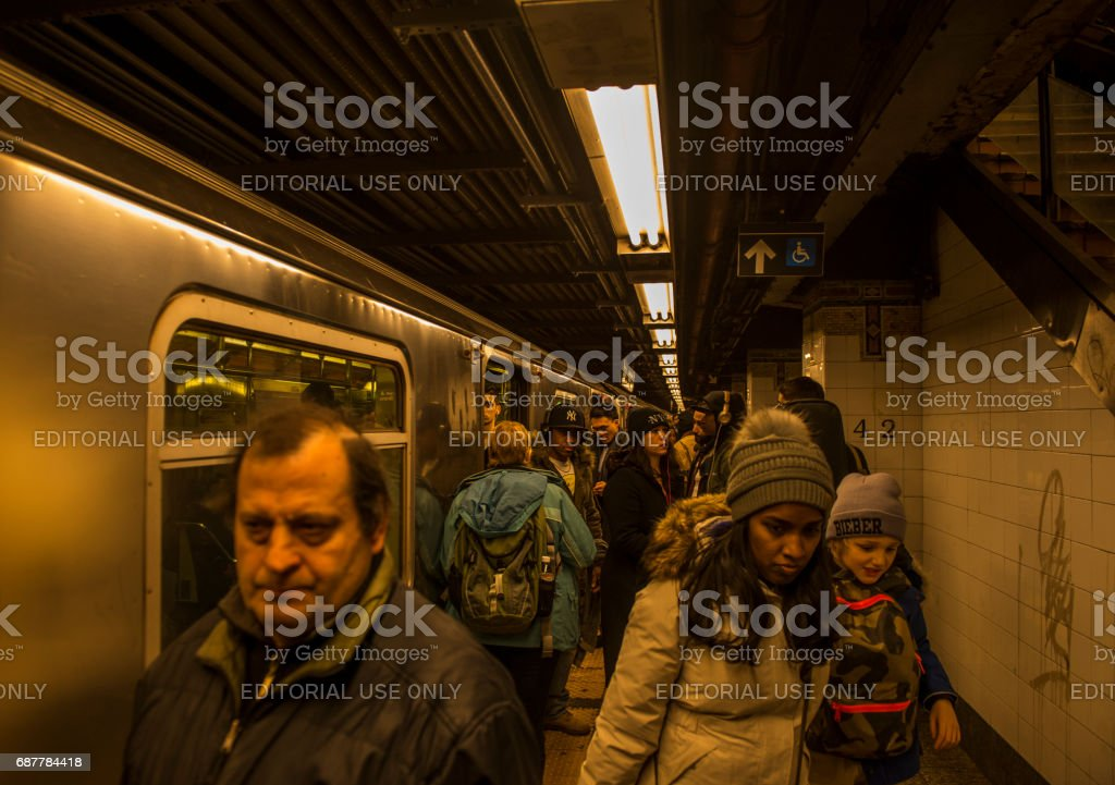 Large group of people in subway platform leaving the train in Manhattan, New York City stock photo