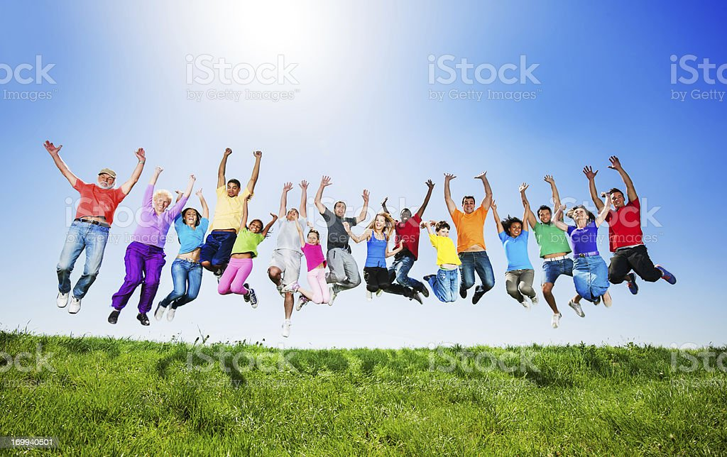 Large group of people jumping against the clear sky. stock photo