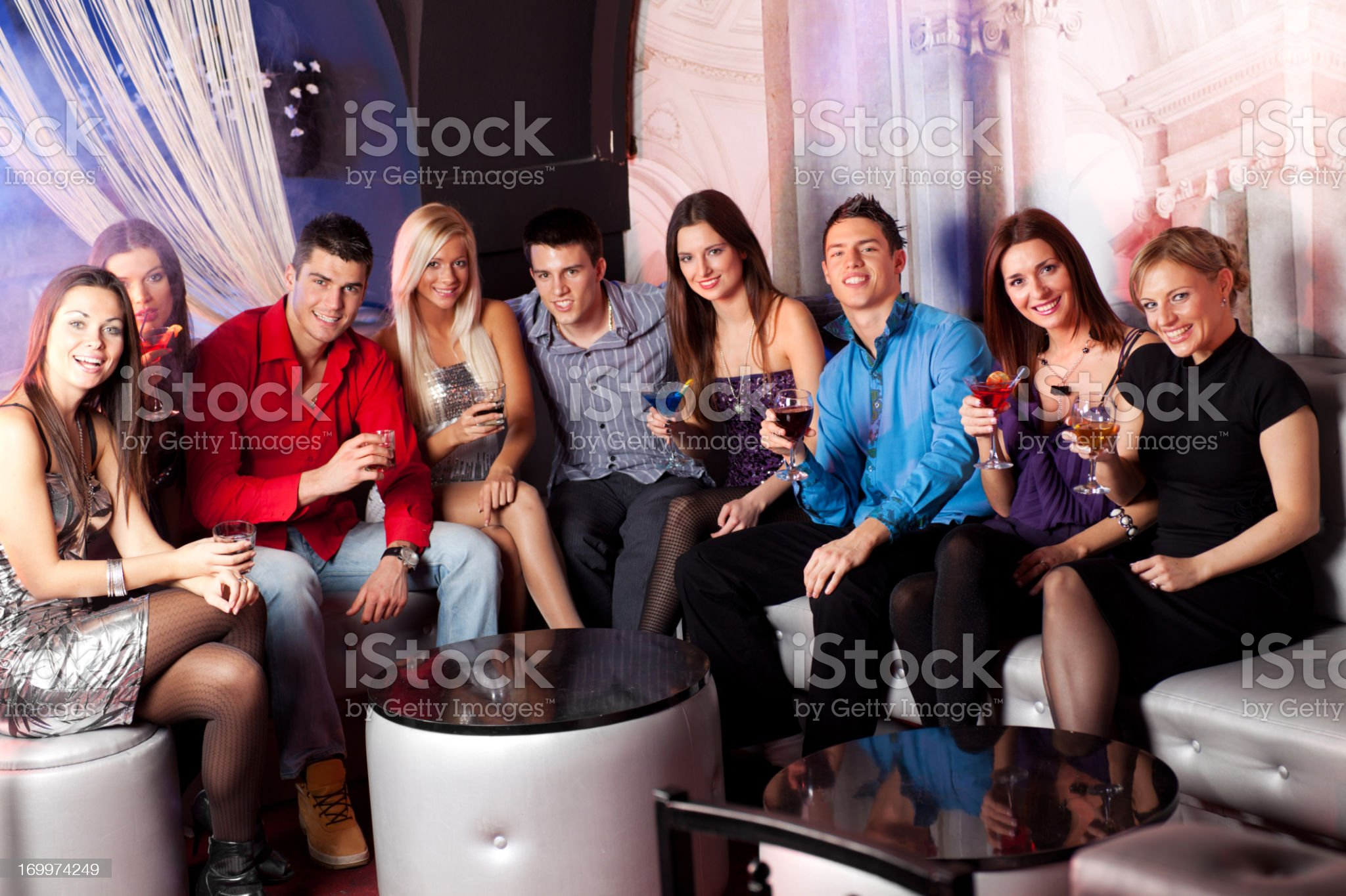 Large group of people sitting at disco club and toasting royalty-free stock photo