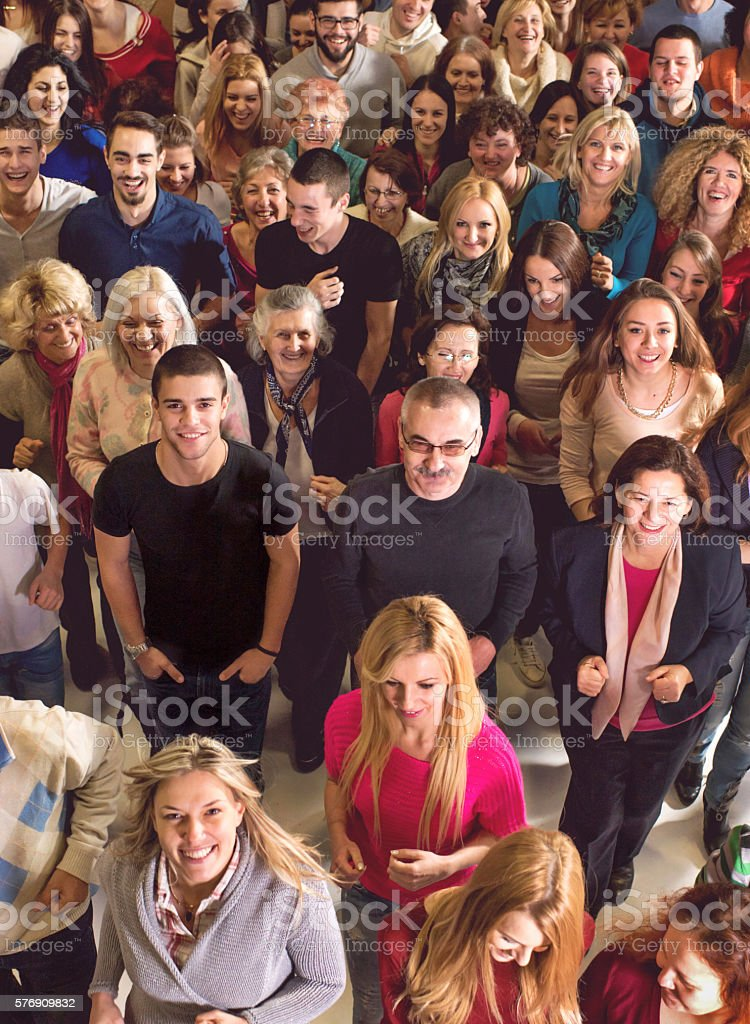 Large group of people standing together and looking at camera. stock photo