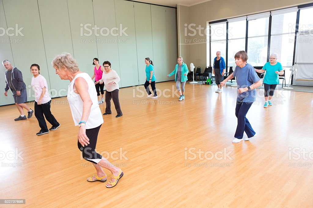 Large group of seniors take line dancing class stock photo