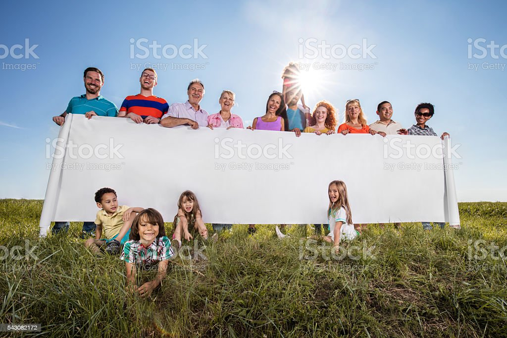Large group of smiling people holding blank placard in nature. stock photo