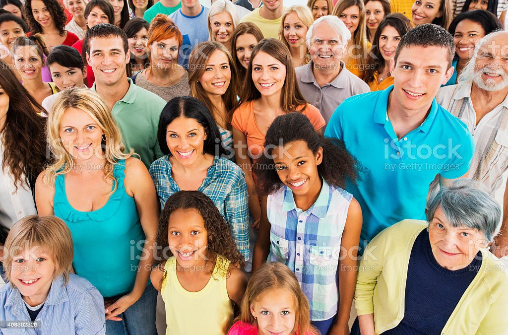 Large group of smiling people looking at the camera. stock photo
