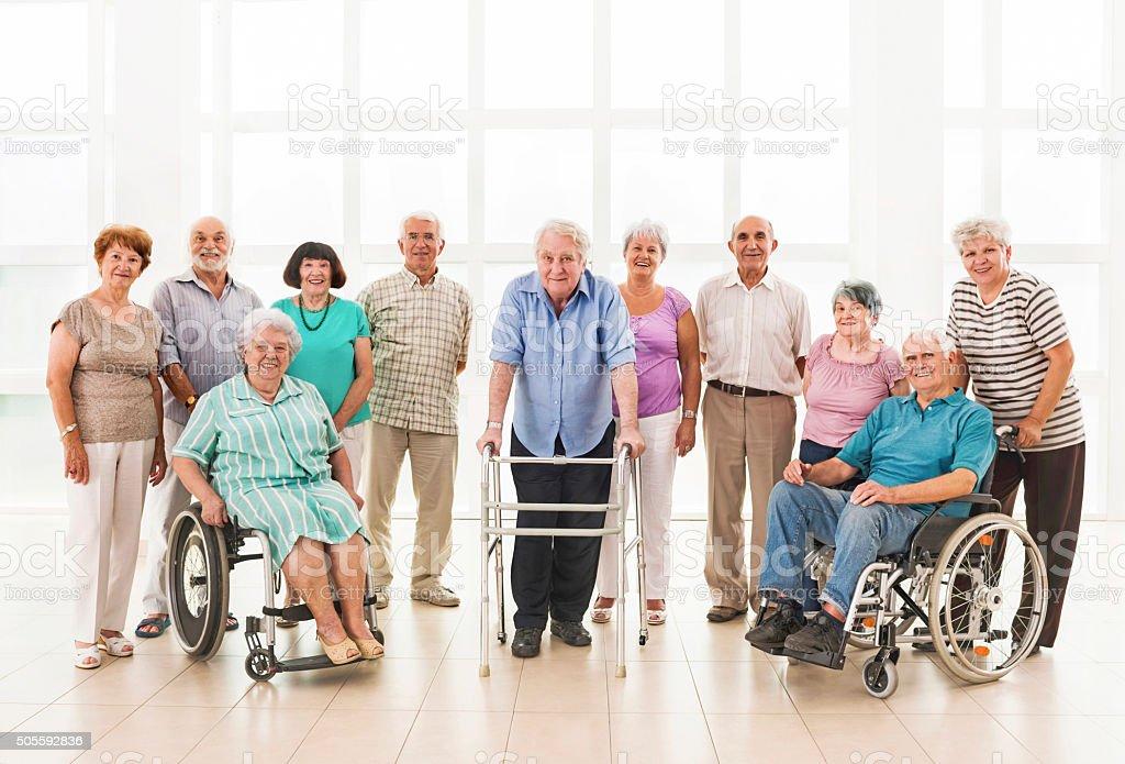 Large group of smiling seniors looking at camera. stock photo