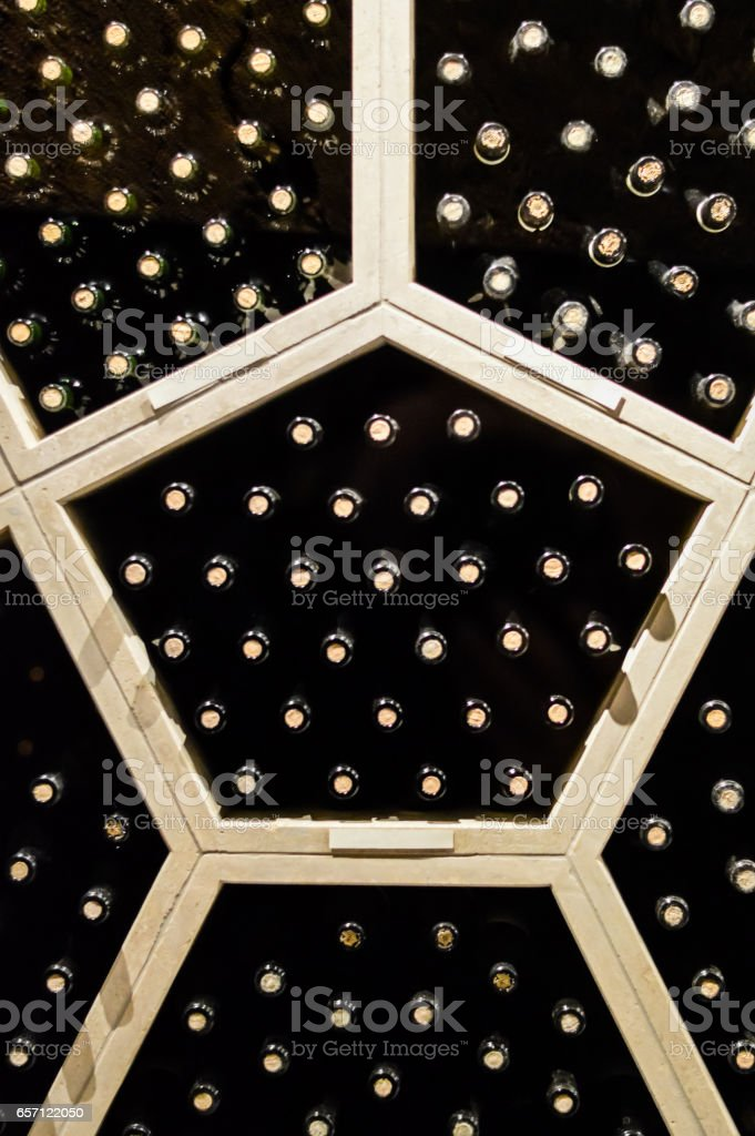 Large group of stacked up wine bottles front view stock photo