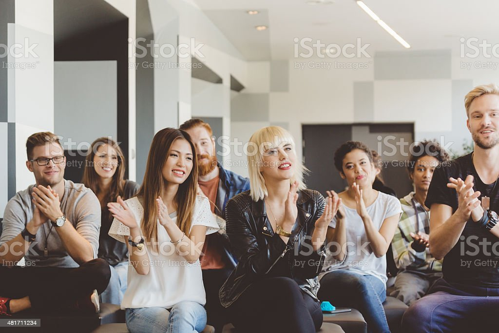 Large group of students on seminar clapping hands stock photo