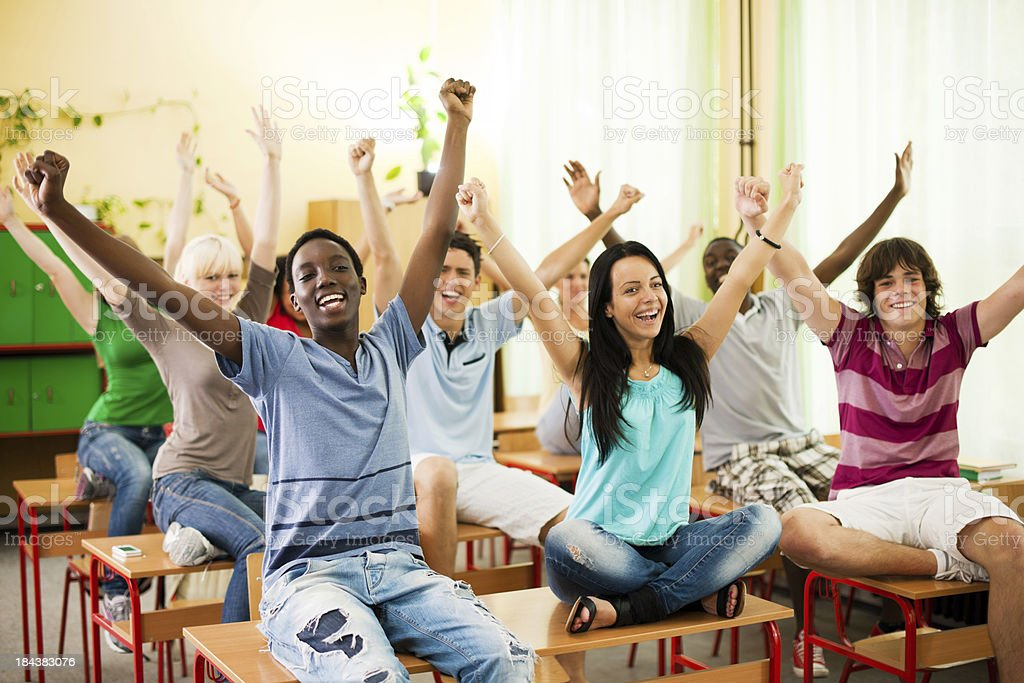 Large group of students sitting on desks with raised arms. stock photo