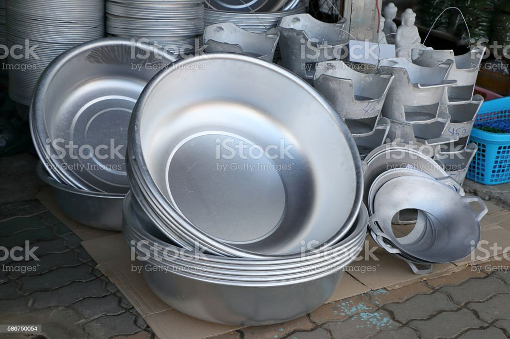 large group of vintage aluminum kitchen utensils in local market stock photo