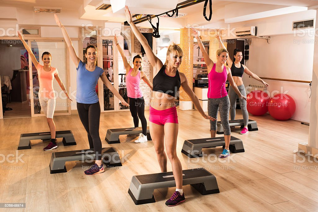 Large group of women exercising on aerobics class at gym. stock photo