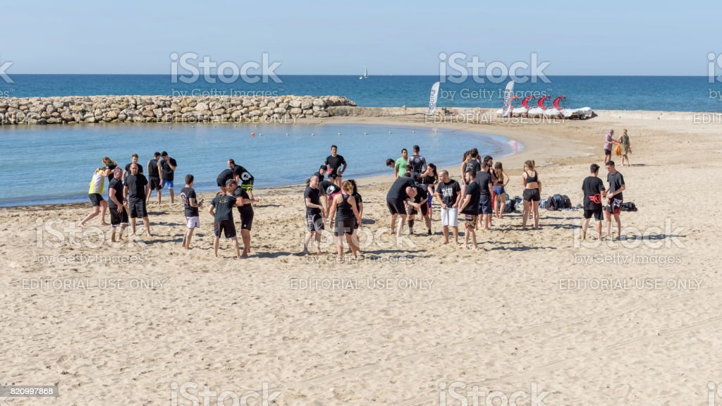 Large group of young people, girls and boys, are engaged in wrestling on the seashore. General plan stock photo