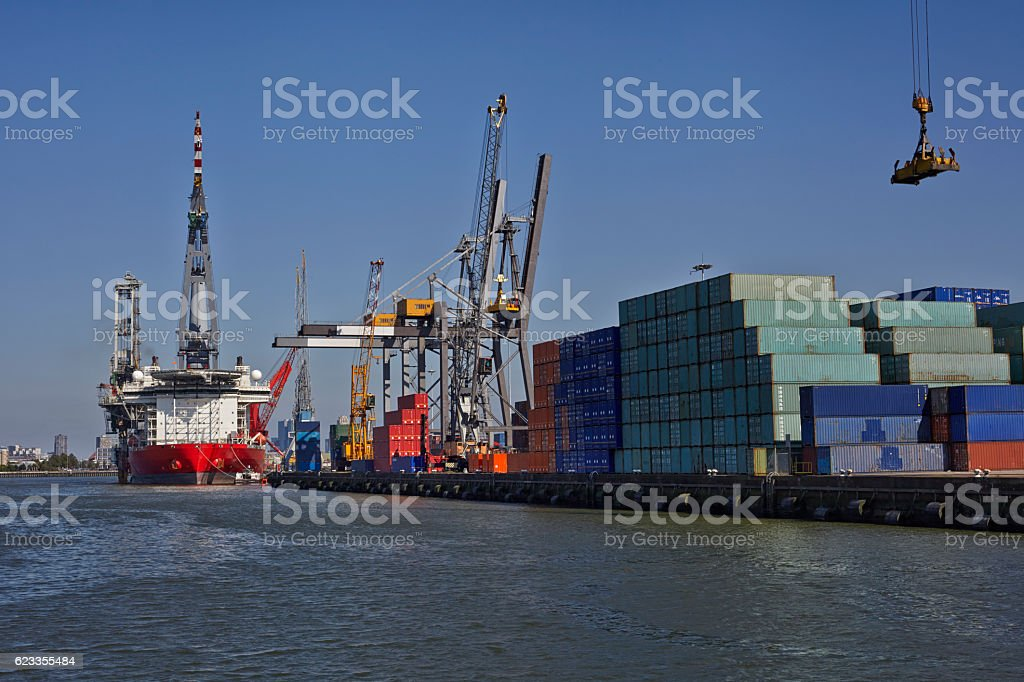 Large harbor cranes loading a large container ship stock photo