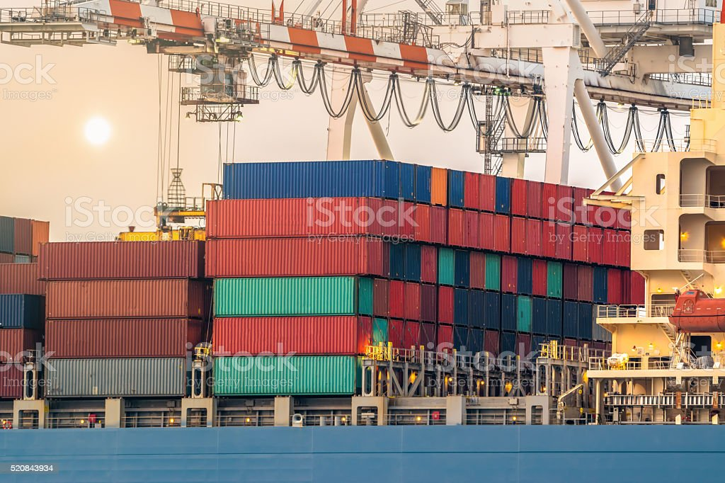Large harbor cranes loading containers in the ships stock photo