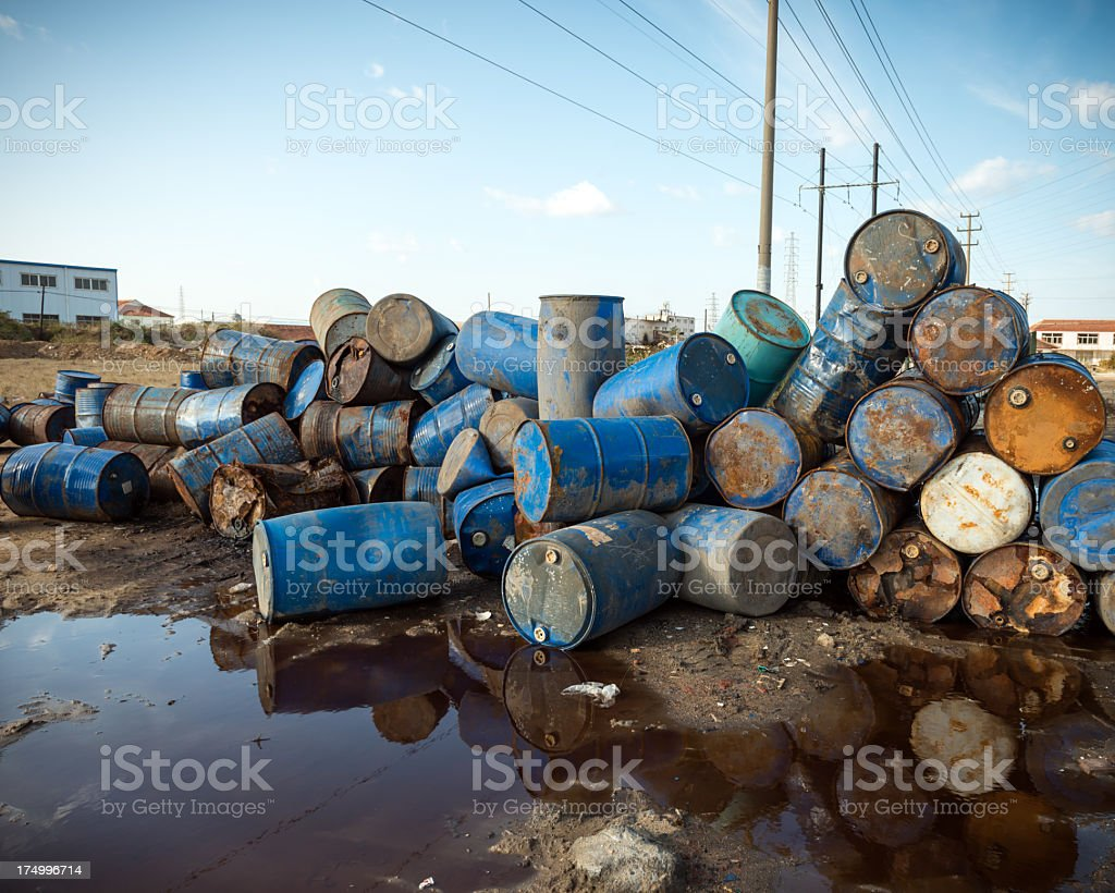 Large heap of rusting oil drums near muddy puddle stock photo