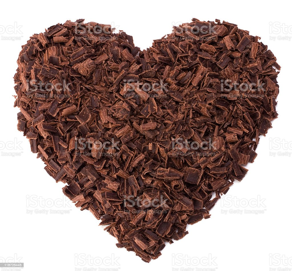 Large heart made of grated chocolate against white back stock photo