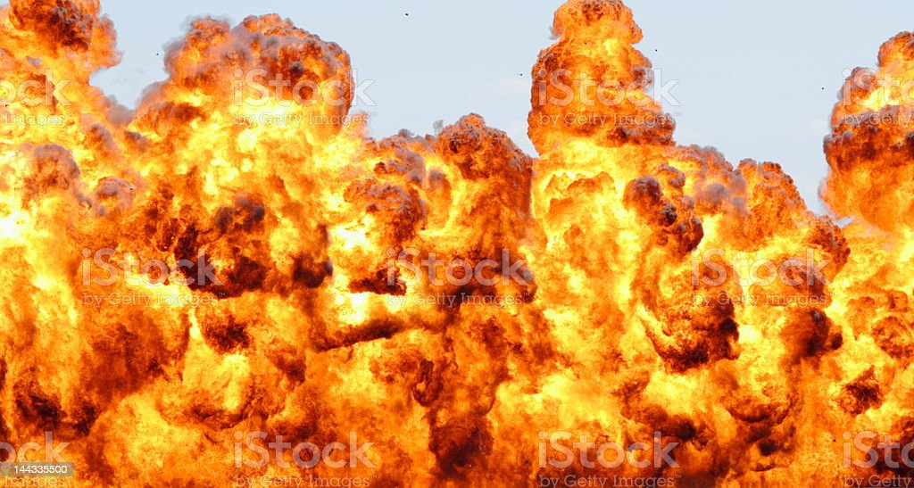 Large hot explosion, debris can be seen in sky stock photo