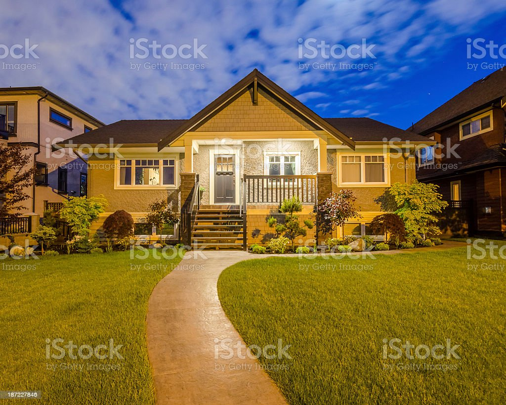 A large house viewed from the garden at dusk stock photo