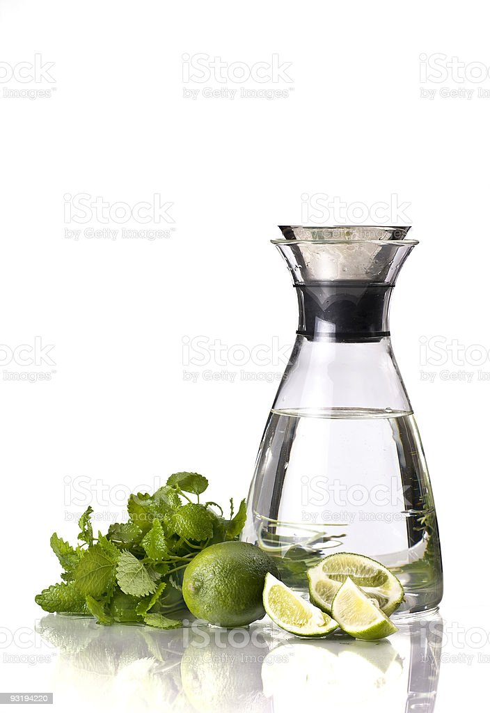 A large jug of water next to green fruit royalty-free stock photo