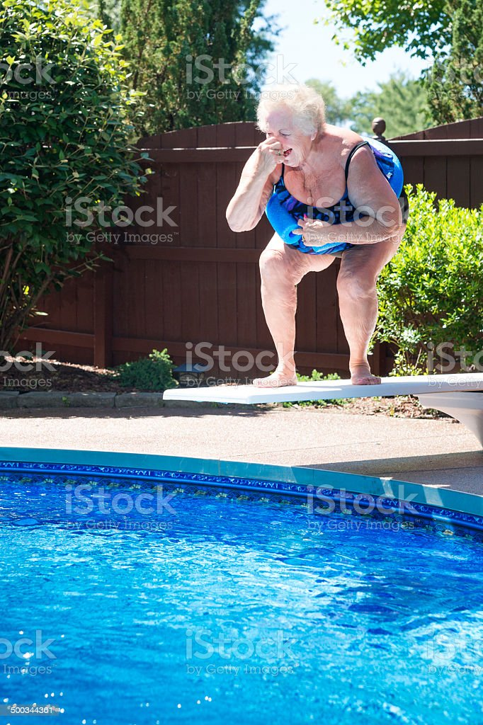 Large lady laughing on diving board stock photo