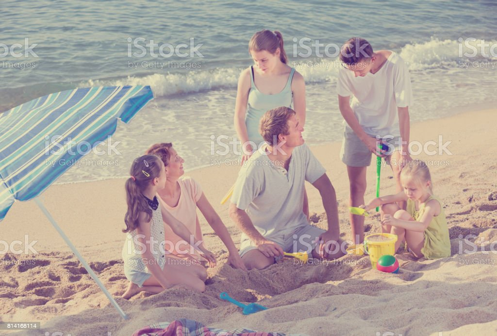 Large laughing family playing active games on beach stock photo
