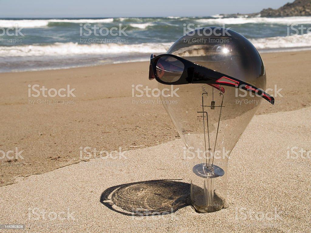 Large lightbulb on the beach wearing sunglasses stock photo