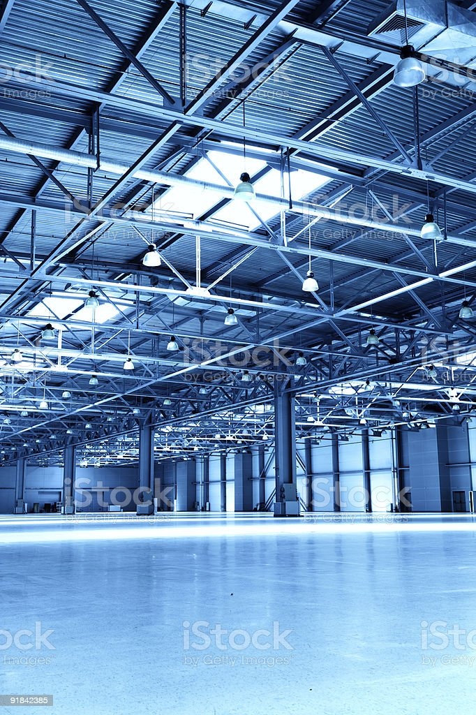 Large, lit up empty warehouse with ceiling beams stock photo