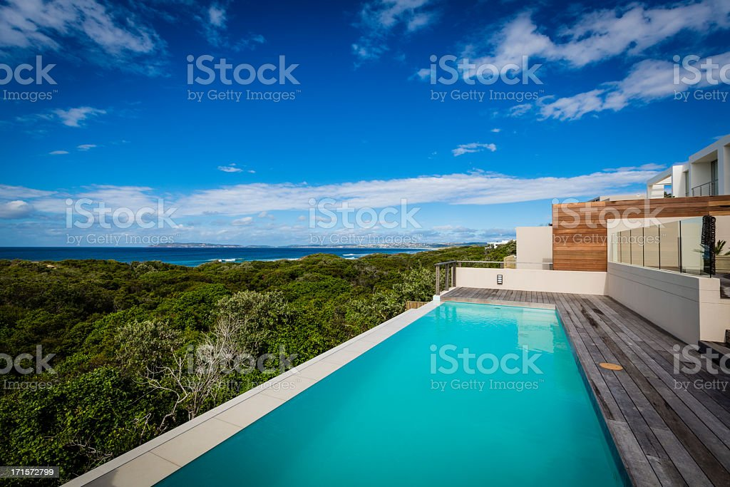 Large luxury villa pool and deck on a cliff with ocean view royalty-free stock photo