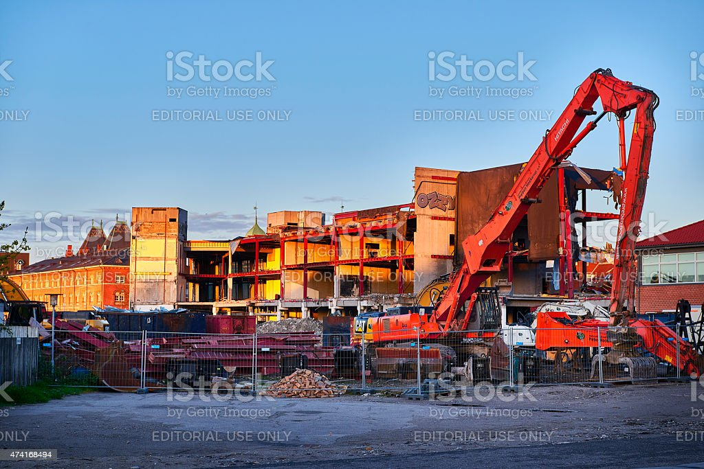 large machines dismantles an office building stock photo