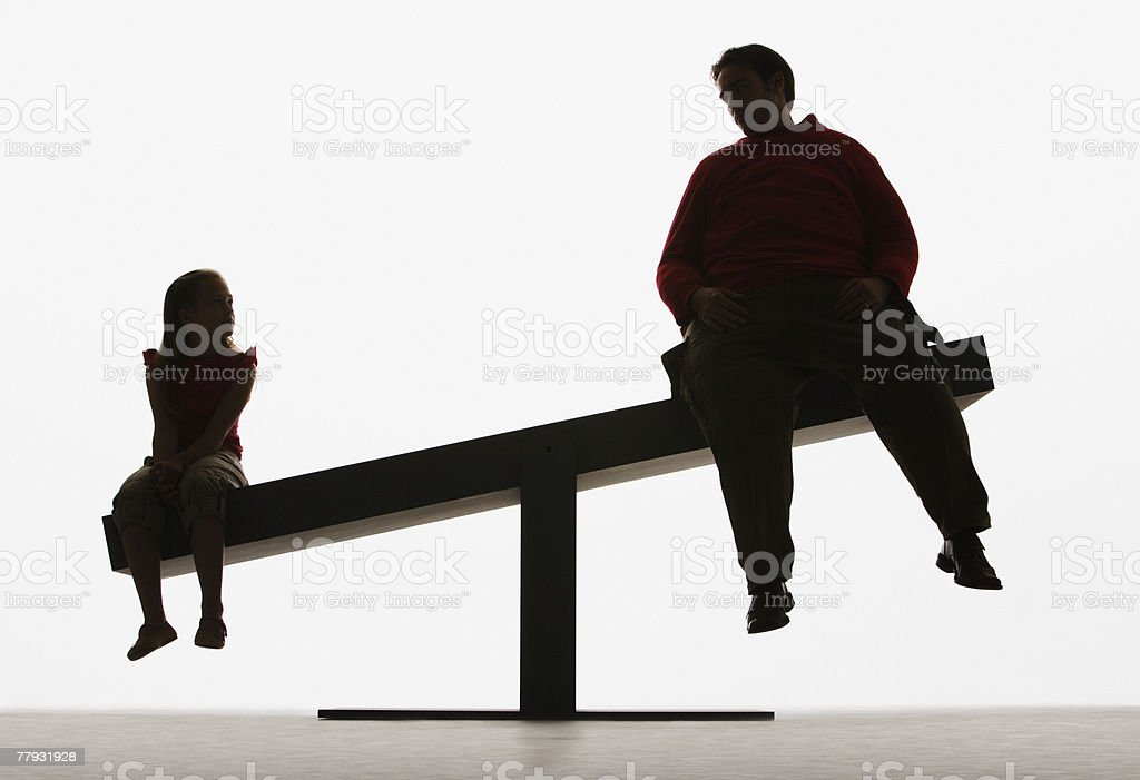 Large man and small girl on unbalanced plank royalty-free stock photo