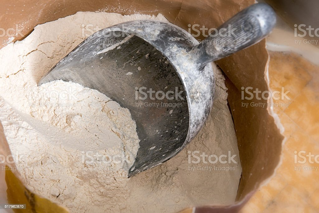 Large Metal Scoop in Paper Bag of White Flour stock photo