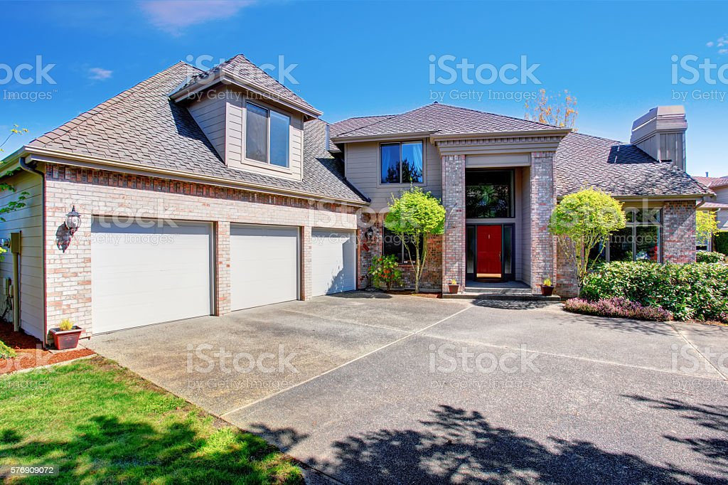 Large modern house with three garage spaces and concrete driveway. stock photo