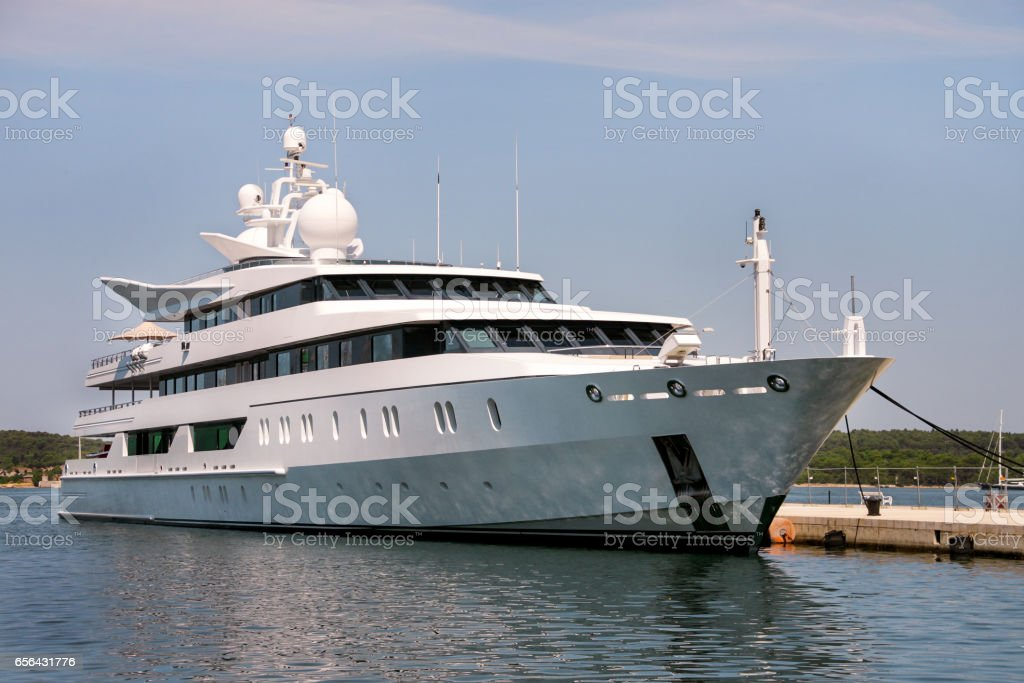 Large modern luxury white yacht and ship anchored in harbor. Large white modern motorboat super yacht and ship in the port city of Pula, Croatia. Yachting concept. stock photo
